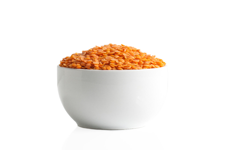 A cup of red lentils isolated on a white background.