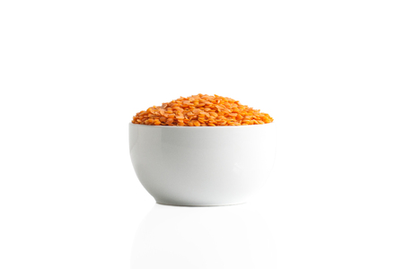 Stack of red lentils in a cup isolated on a white background.