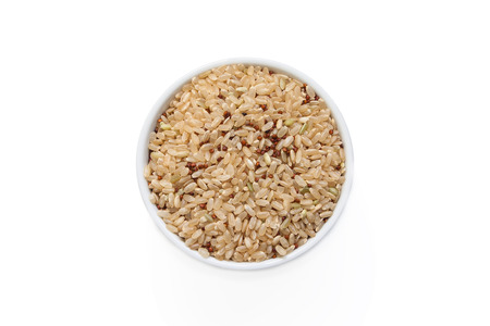 Quinoa and brown rice in a cup from above isolated on a white background.