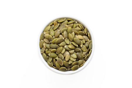 Pumpkin seeds in a cup from above isolated on a white background.