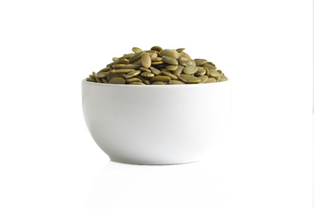 A cup of pumpkin seeds isolated on a white background.