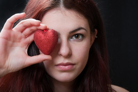attractive young woman holding a toy heart photo