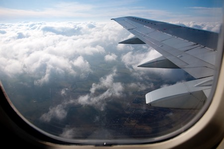 airplane window: wings of aircraft and view from above Stock Photo