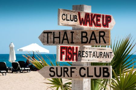 Wooden signboard from four arrows on the beach Stock Photo