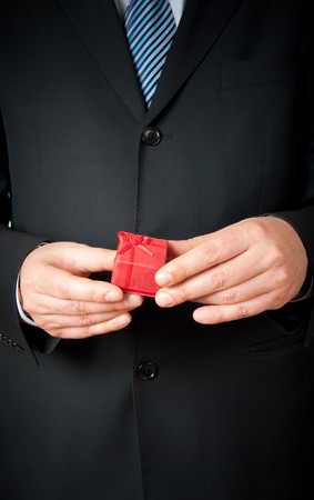 Businessman holding a small red gift box photo