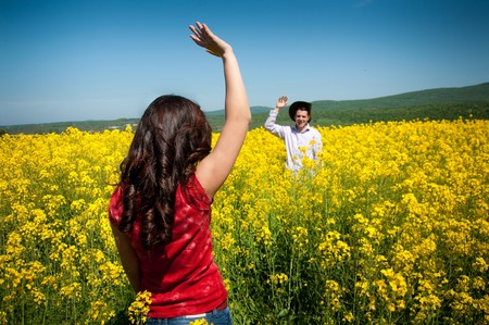 young man and woman in yellow field photo