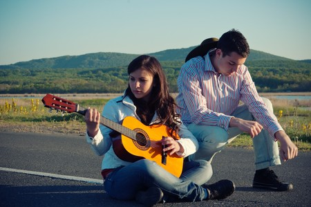 Young Couple Sitting in Middle of Road with Guitar photo