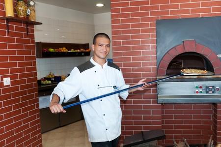 hombre cocinando: hombre joven cocina pizza