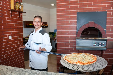 pizza oven: young man cooking pizza Stock Photo