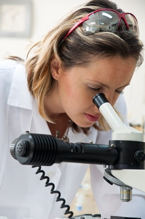 Scientist looking into a microscope photo