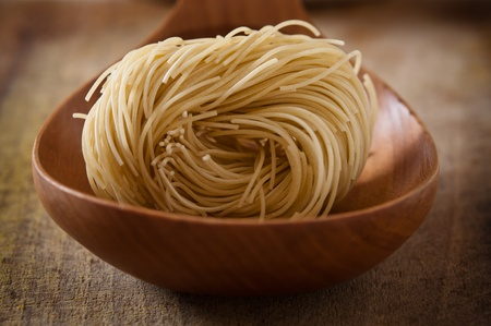 Noodles on wooden spoon photo