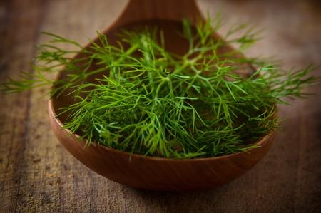 Green fennel in a wooden spoon photo
