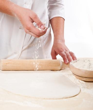 harina: manos de la mujer amasa la masa