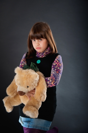 sad girl with her teddy bear Stock Photo