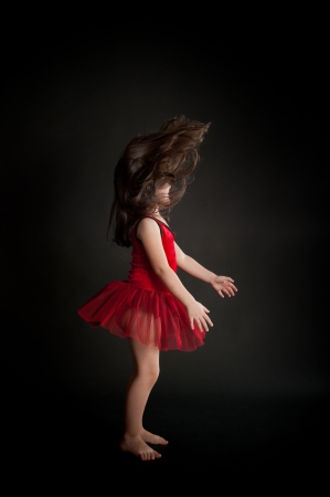 cute little girl dancing in red dress photo