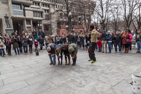 contortionist: Boston, MA, USA - March 1, 2014: People in winter clothes are watching the street performance at Freedom Trail near the Boston City Hall