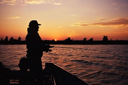 fisherman casting at sunset in hopes of catching one more fish  Banco de Imagens