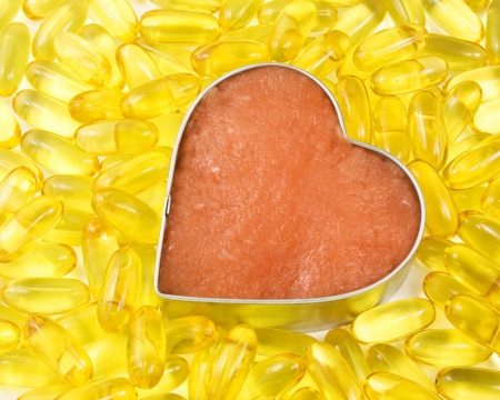 silver outlined salmon heart surrounded by salmon oil Stock Photo - 4728729