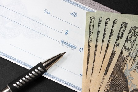 pen laying on top of blank check. recent withdrawal of several twenty dollar bills are next to the check.