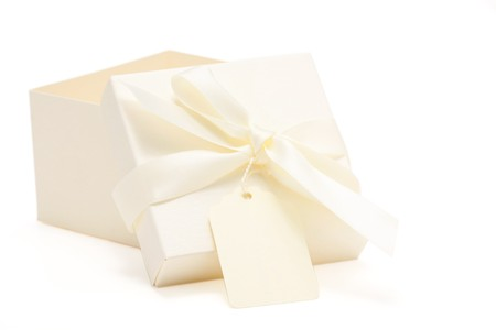 partially opened cream colored gift box with attached bow and name tag; white background  photo