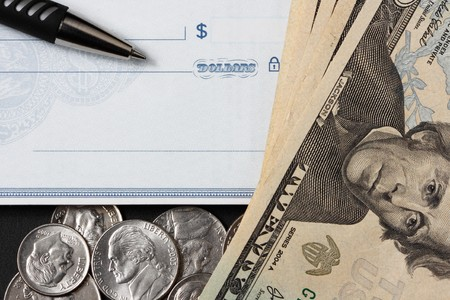 blank check with pen on top. twenty dollar bills and coins lay at side on bottom of the check photo