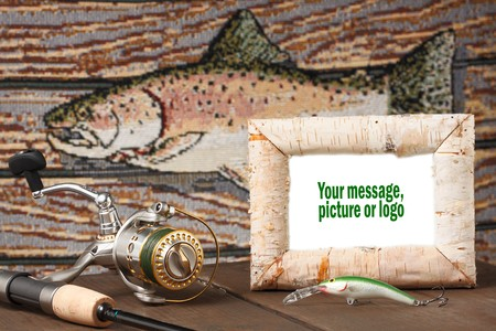 Reel and lure on table with fish in background. White picture in birch frame can be changed to fit designers requirements. photo