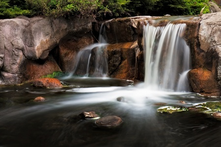 enhances: The waterfalls at Lake Katherine tumble into the stream with creamy and silky smoothness  Timelapse photography enhances the moving water  Stock Photo