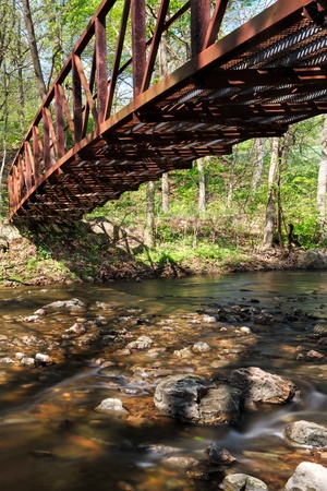 meanders: a rusty foot bridge over a rocky creek  timelapsed photography details the fast moving water in creamy silyness as it meanders its way around the rock filled creek