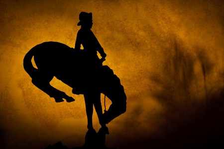 bucking bronco: Silhouette of cowboy on a bucking bronco  orange yellow sunset background with shadows of prairie grass
