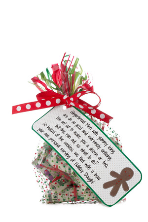 cellophane: clear cellophane bag colored with a green and red stripes and dots filled with money  gift note on outside of bag  smiling gingerbread man on the note