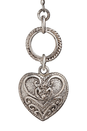 silver heart pendant with ornate design on white background