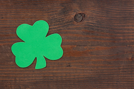 weather beaten: A green shamrock on aged weather beaten brown knotted wood.