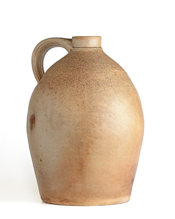 Oval shaped tan and yellow clay jug with handle, white background, angular view.