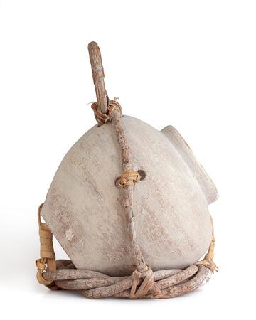 Cream colored birdhouse jug partially wrapped in a twig holder held together with leather straps. white background, profile view. photo