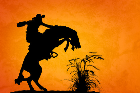 Silhouette of cowboy reigning bucking bronco spooked by something in the nearby sagebrush  Sunset orange yellow textured background  photo