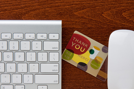 Thank you gift card in between keyboard and mouse on a brown wooden grain desktop  版權商用圖片