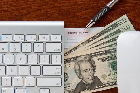 deposit slip: online banking  keyboard and mouse frame deposit slip and twenty dollar bills  pen points to deposit slip all are on top of a brown grain wood