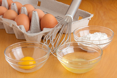 powdery: Separated cracked eggs in glass bowls, flour in a glass bowl, a silver whisk, and carton of eggs all on a cutting board  Stock Photo