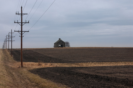 On a cold cloudy day in autumn, telephone poles lead the way to a withered barn.  Th barn which stands in recently plowed farm fields is the only structure visable.