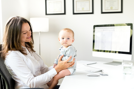 Businesswoman in Office with Baby