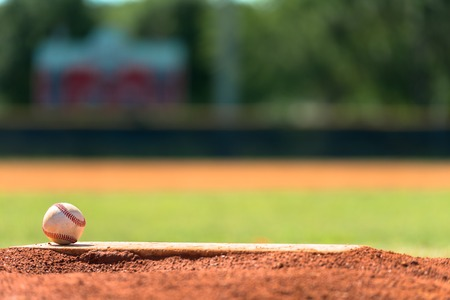 pitchers mound: Baseball on a pitchers mound with field in background