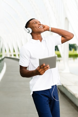 Black, African American college student wearing headphones and listening to music on a digital tablet computer Фото со стока - 43366872