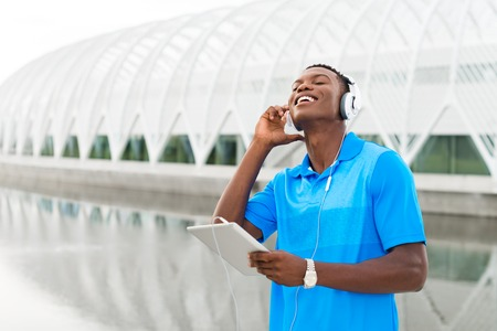 black male: Black, African American college student wearing headphones and listening to music on a digital tablet computer