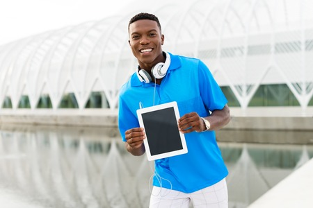 Black, African American college student wearing headphones and showing a digital tablet computer