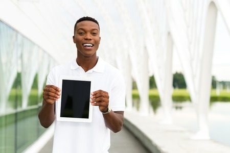 black male: Black, African American college student showing a digital tablet computer