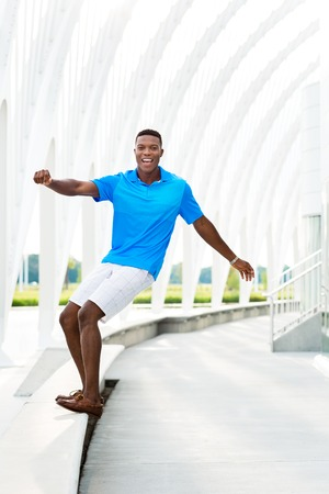 goofing: Black, African American college student pretending to surf modern architectural building