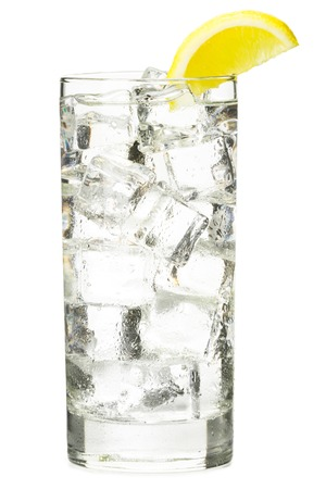 lemon wedge: Tall clear sparkling vodka tonic or soda soft drink with lemon wedge garnish isolated on white