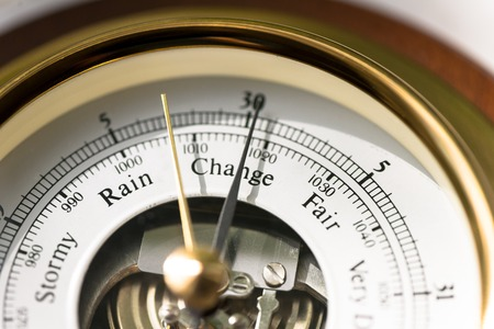 inches: Close up of aneroid barometer with needle at 30.025 inches