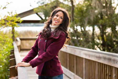 Happy young woman dressed for cold weather on nature walk near river