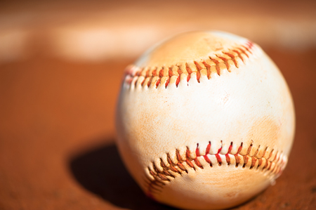 Close up shot of baseball with red clay dirt in background